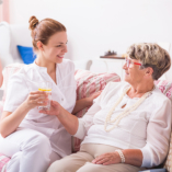 caregiver serving water to senior woman