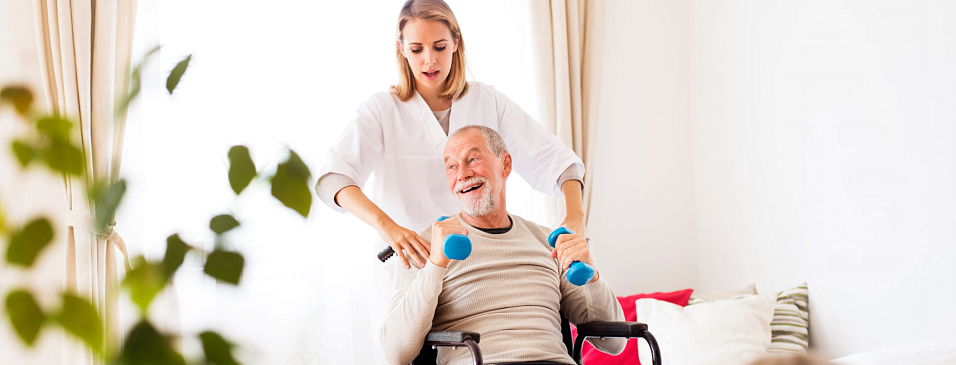 caregiver helping old man to excercise