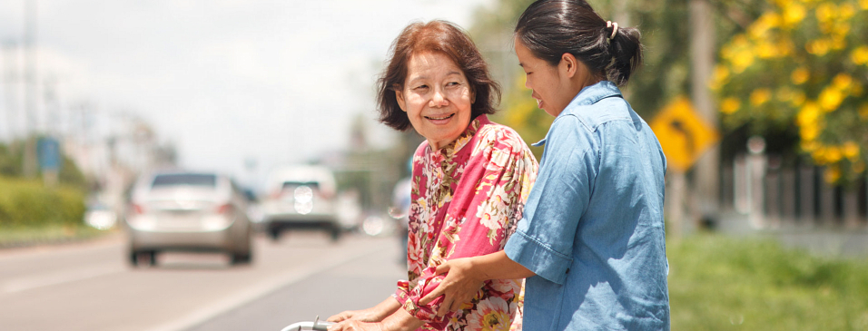 caregiver helping old woman to across the road