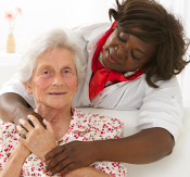 caregiver and old woman hugging each other